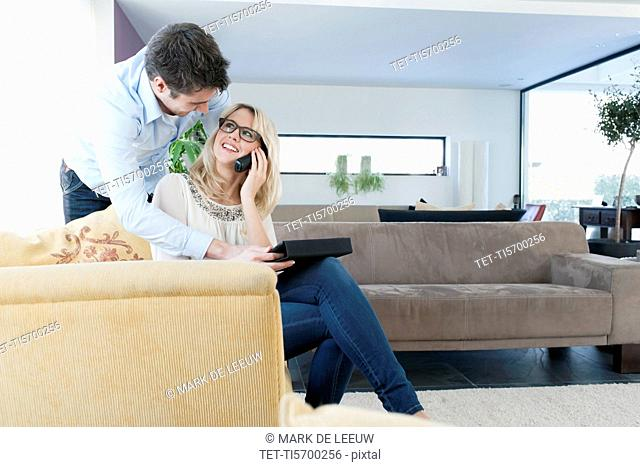 Woman talking on cell phone, man using tablet PC at home