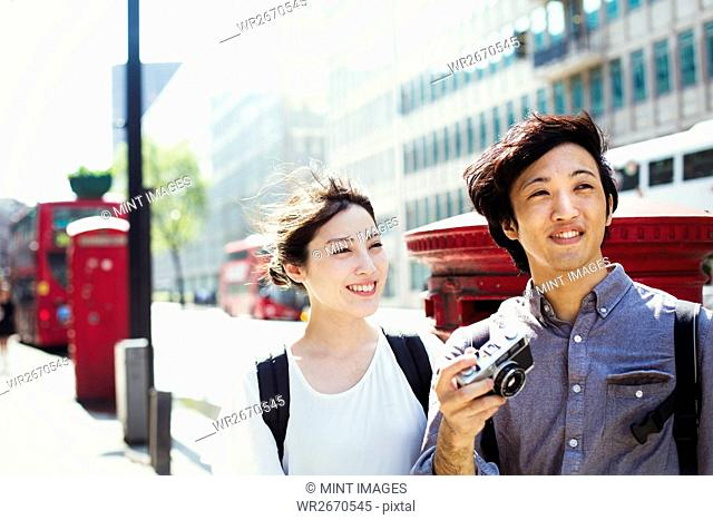 Young Japanese man and woman enjoying a day out in London, walking down a street