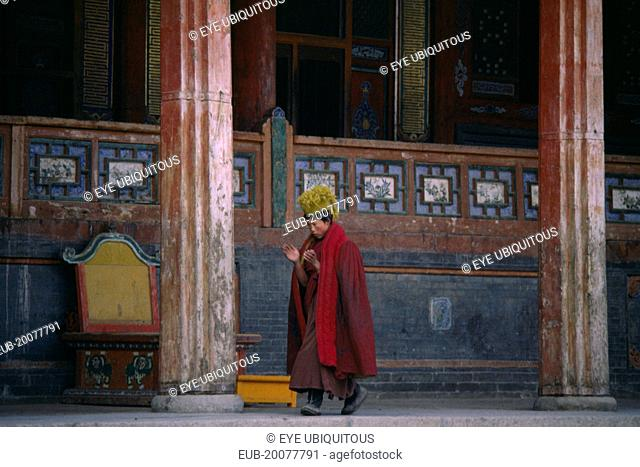 Tibetan Yellow Hat Buddhist monk calling other monks to prayer