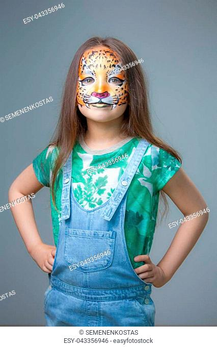 Beautiful little girl with aqua makeup on her face in the form of a tiger
