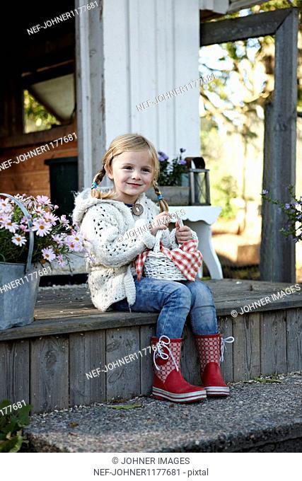 Girl holding eggs in basket, smiling