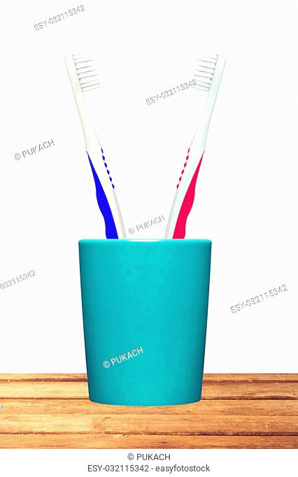 Toothbrushes in glass on table isolated on white background