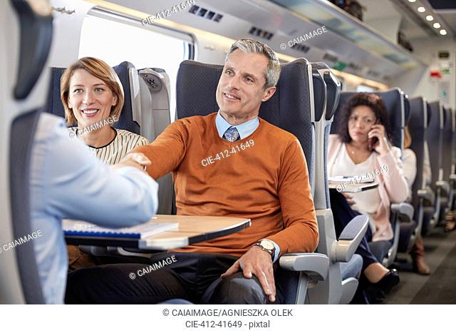 Business people handshaking on passenger train