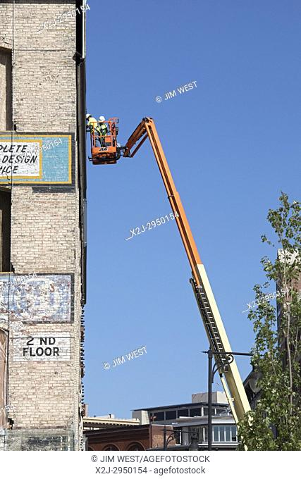 Grand Rapids, Michigan - Two men on a cherry picker work on the side of an old downtown building