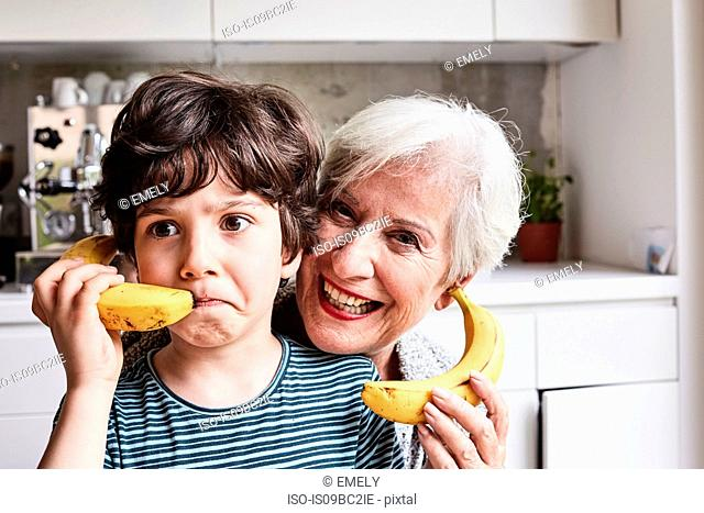 Grandmother and grandson fooling around, using bananas as telephones, laughing