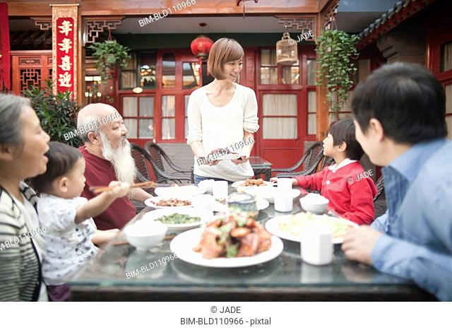 Chinese mother serving family outdoors