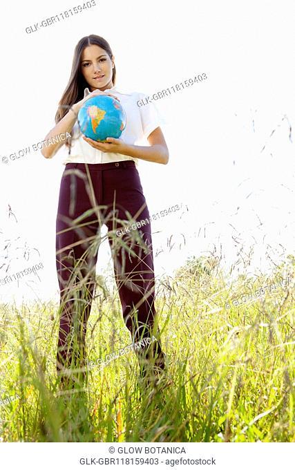 Businesswoman holding a globe in a field
