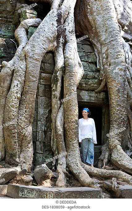 Tourist outside temple entrance overgrown with gigantic tree roots in ancient city of Angkor, Angkor Wat, Siem Reap, Cambodia