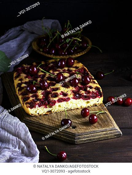 baked cake with cherries on a brown wooden board, next to fresh berries