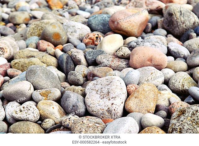 Background of colourful beach pebbles of different shape and size
