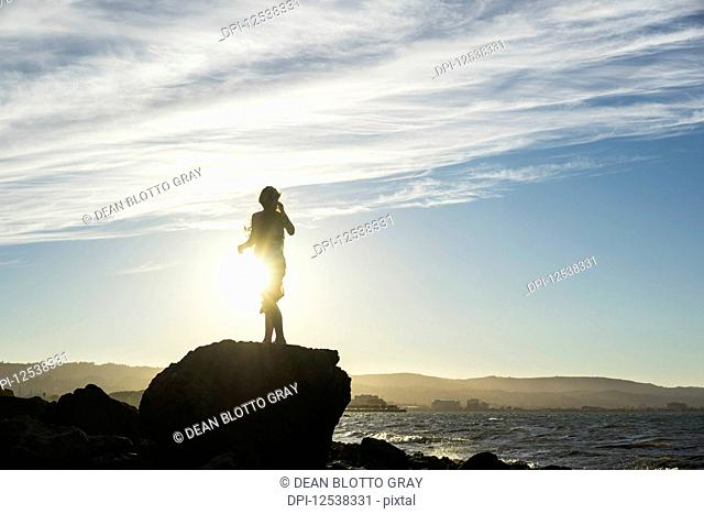 A woman stands on a rock looking out along the coast at sunset, silhouetted and backlit by the sunlight; San Mateo, California, United States of America