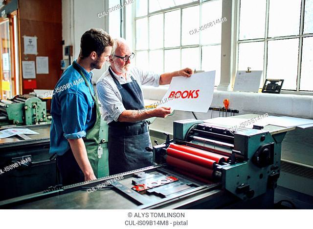 Senior craftsman/technician showing young man letterpress print in book arts workshop