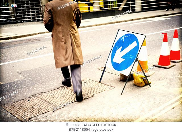Works signs on the street and an unrecognizable man crossing. London, England, UK, Europe