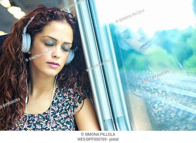 Portrait of young woman with headphones relaxing in a train