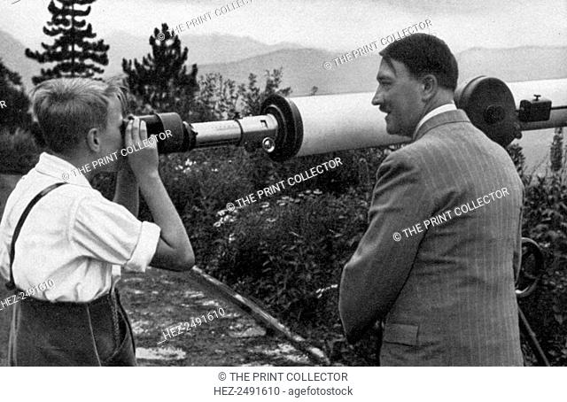 Adolf Hitler at his residence in Obersalzberg, Bavaria, Germany, 1936. Hitler (1889-1945) with a boy looking through a telescope at the Nazi leader's mountain...