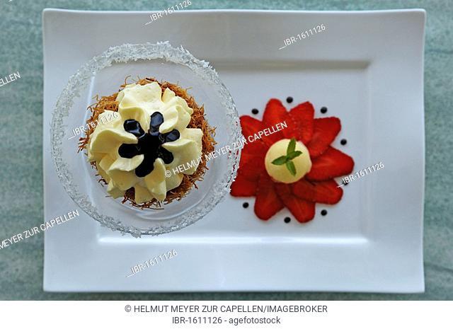 Dessert, passion fruit mousse on Kataifi noodles and melon icecream on strawberries on a white plate, Haute Cuisine, Auberge de la Ferme Hueb