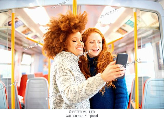 Friends taking selfie with mobile phone on train, London