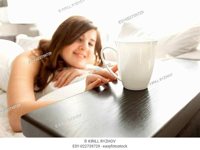 woman lying in bed and taking cup of coffee