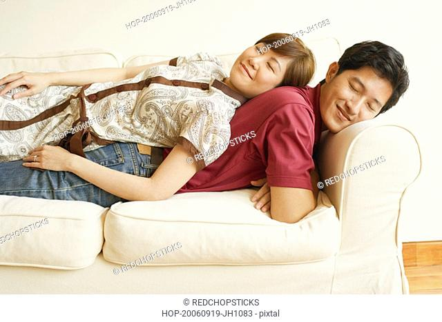 Side profile of a young couple sleeping back to back on a couch