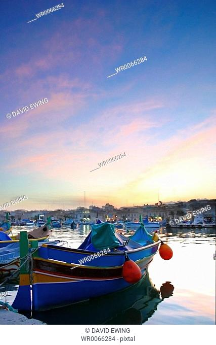 Brightly painted Maltese boats on blue water in summer, Malta