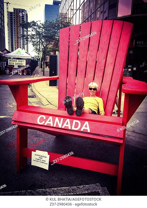 A woman sits in an oversized, giant adirondack chair set out for a street party, Ontario, Canada