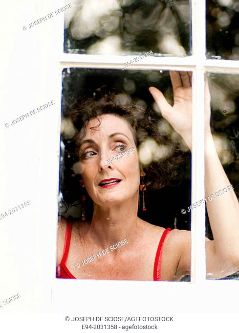A 51 year old brunette woman looking out of a window