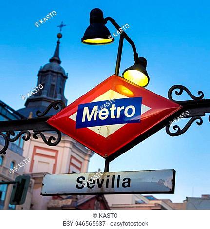 Detail of Vintage Sevilla Metro Station Sign in Madrid Spain, illuminated in dusk
