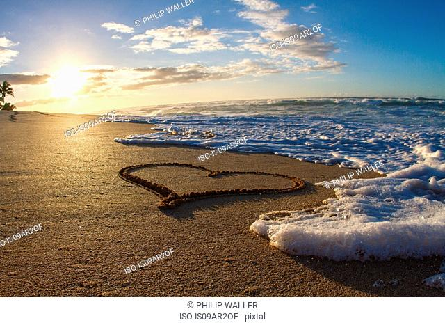 Heart, drawn in sand, sunset