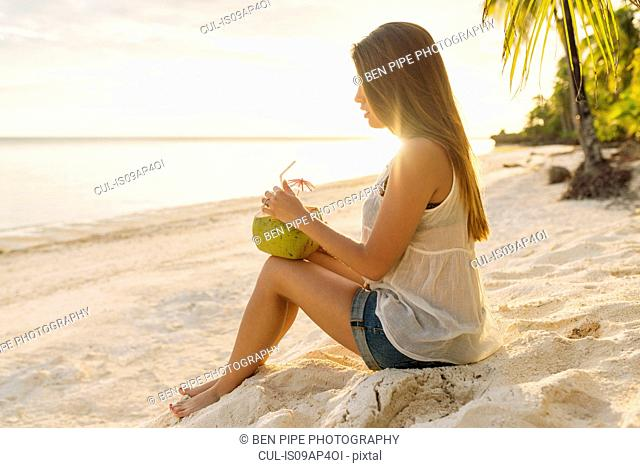 Young woman drinking coconut milk on Anda beach, Bohol Province, Philippines