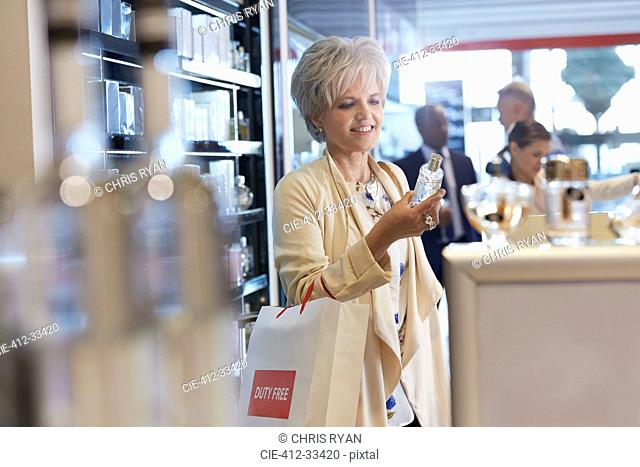 Smiling woman shopping for perfume in duty free shop