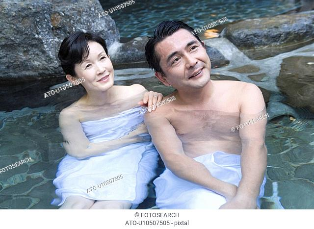 Mature Adult Couple Soaking in a Hot Spring Together, Front View, Three Quarter Length, High Angle View