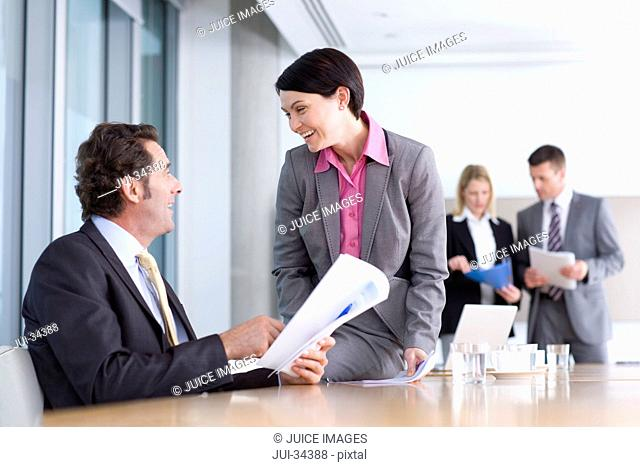 Businessman and businesswoman with report laughing in conference room