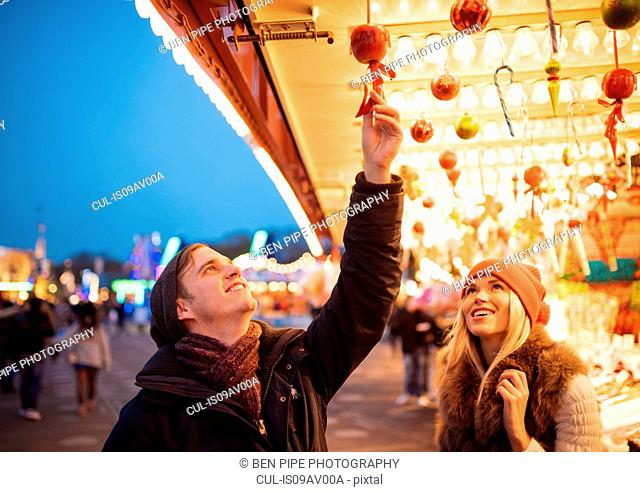 Young couple choosing baubles at xmas festival in Hyde Park, London, UK
