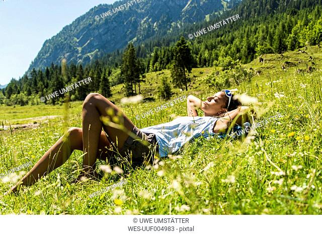 Austria, Tyrol, Tannheim Valley, young woman relaxing in meadow