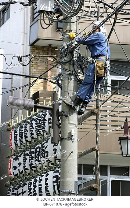 Japan, Tokyo: Worker on an electrical pole in Asakusa
