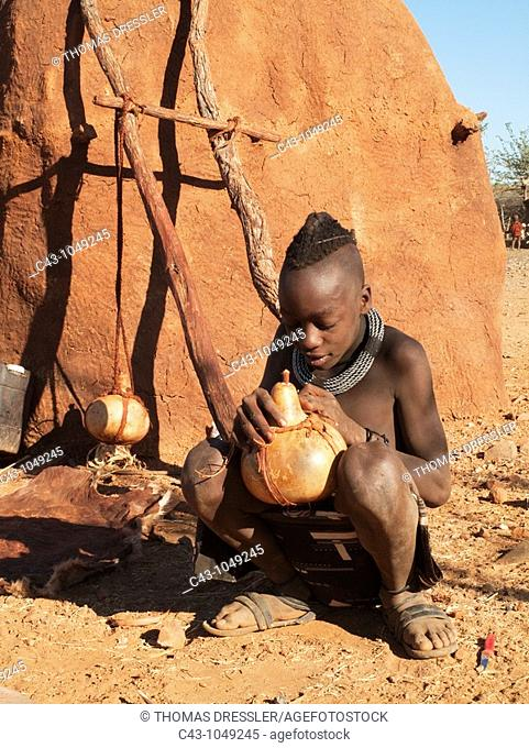 Namibia - Himba boy with the typical single plait hairstyle of the young boys repairing a pot used for butter fat  In a village near the Epupa Falls  Kaokoland