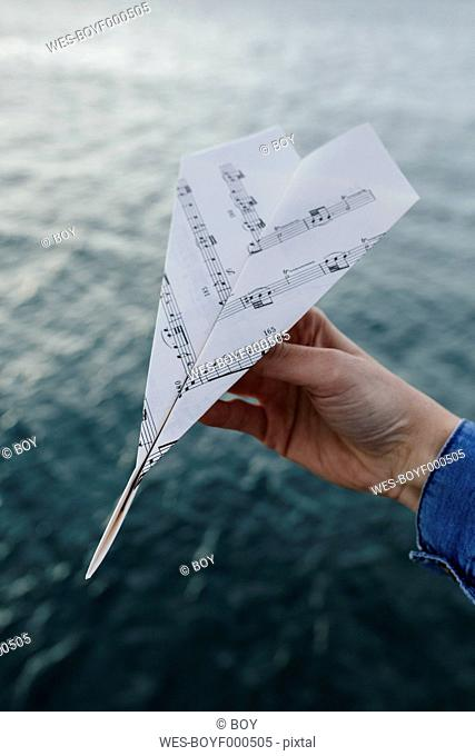 Hand at the water holding paper plane made of music sheet