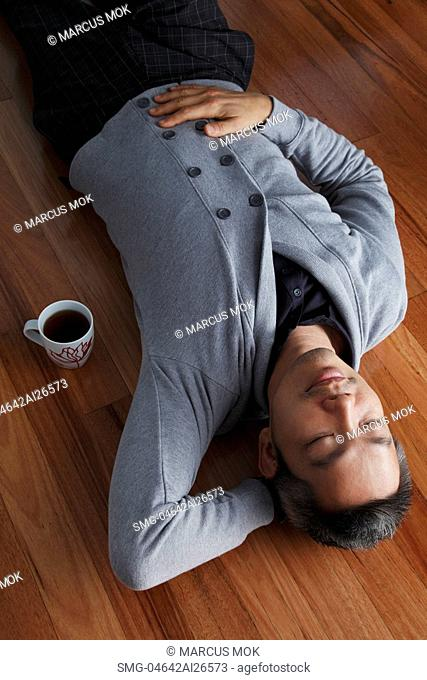 Chinese man laying on floor relaxing