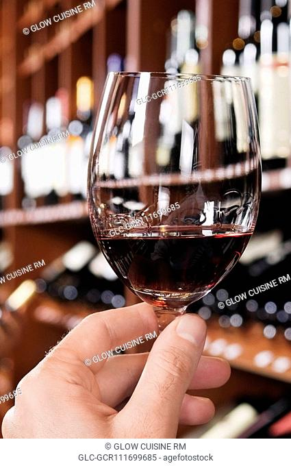 Man's hand holding a wine glass in a bar
