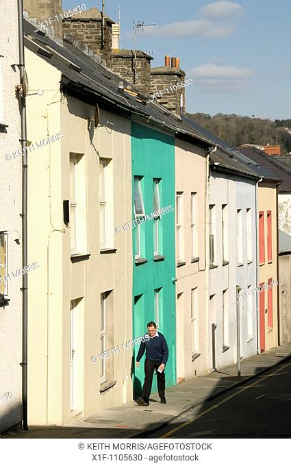 Man walking past a row of terraced houses in Aberystwyth Wales UK
