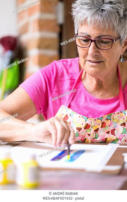 Senior woman painting an abstract picture