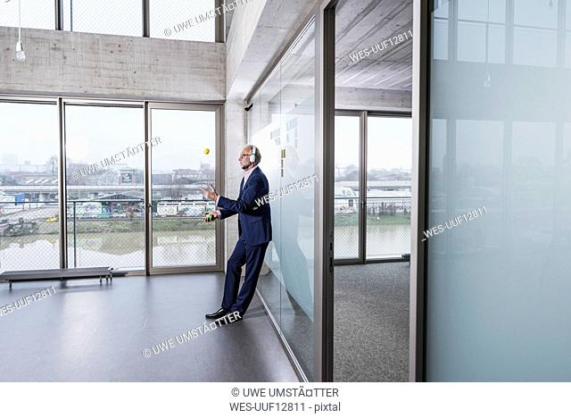 Mature businessman listening to music on headphones juggling with balls