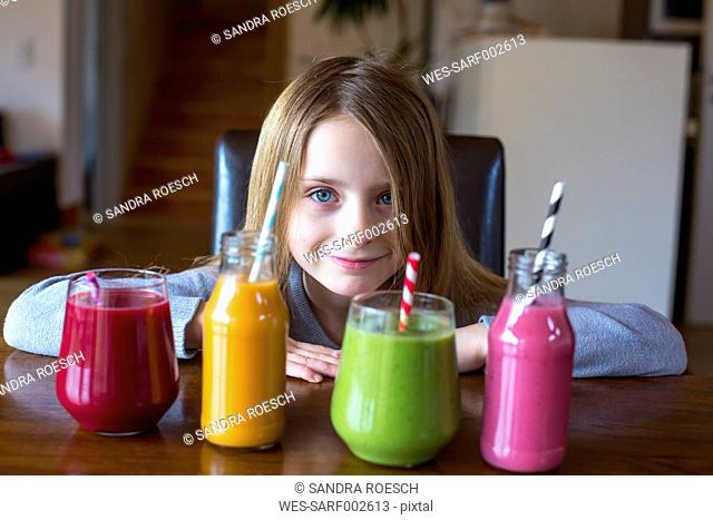 Portrait of smiling girl sitting at table with four different smoothies at choice