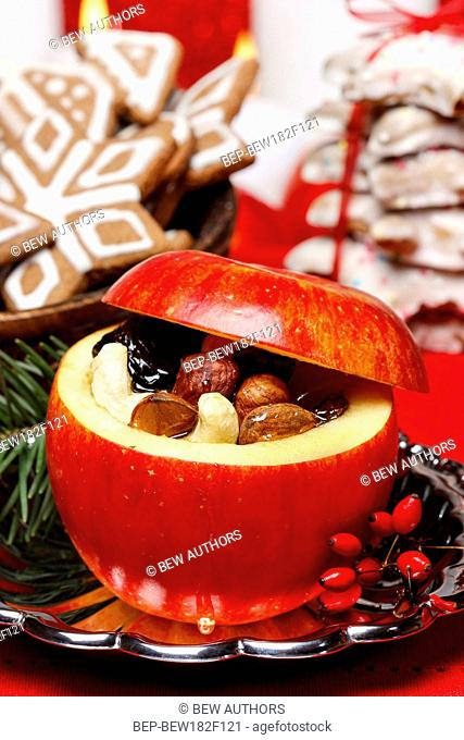 Red christmas apples stuffed with dried fruits in honey. Gingerbread cookies in the background