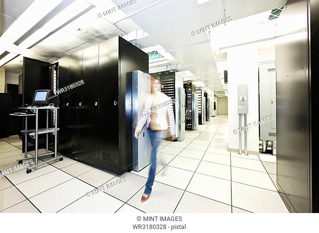 Computer server room racks with technician in background