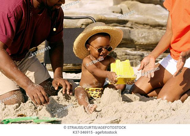 Black family on the beach with young boy building sandcastle
