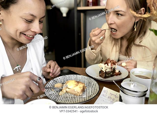 stylish women eating sweet cake in café in Munich, Germany