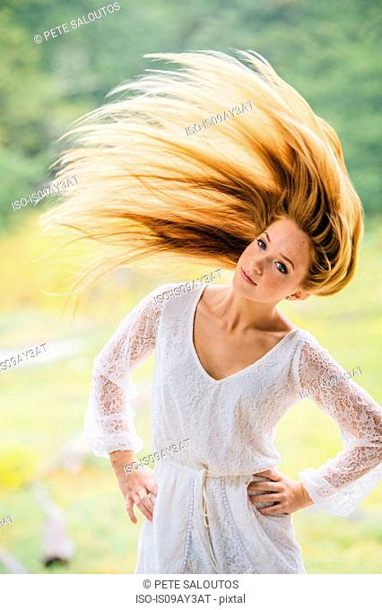 Portrait of teenage girl shaking head of long red hair in park