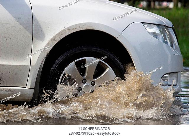 cars driving on a flooded road during a flood caused by heavy rain