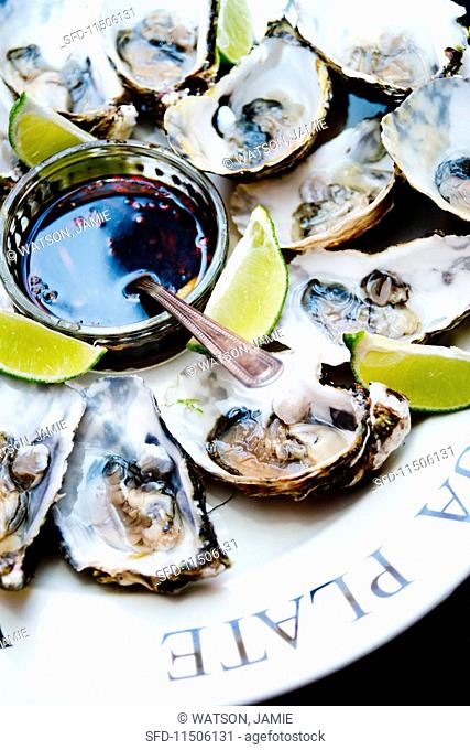 Fresh oysters on a plate with lime wedges and soya and ginger dip